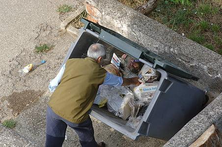 man pickup something in garbage