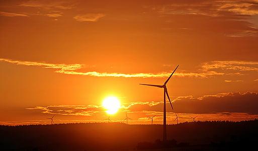 windmills under orange sky during golden hour