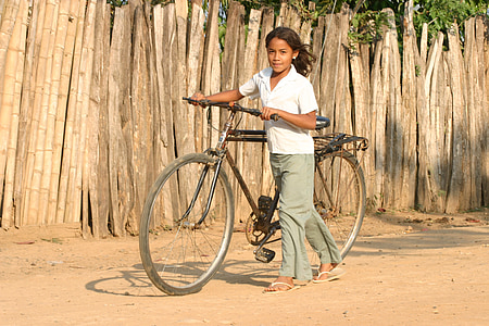 girl carrying black bicycle