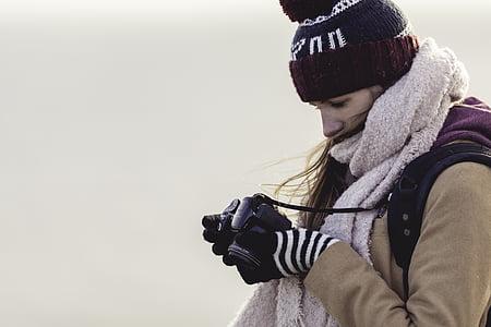 woman looking at the black DSLR camera