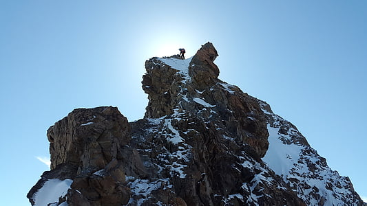 man on top of snow covered mountain