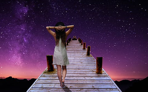 woman holding the back of her head while walking on dock during nighttime