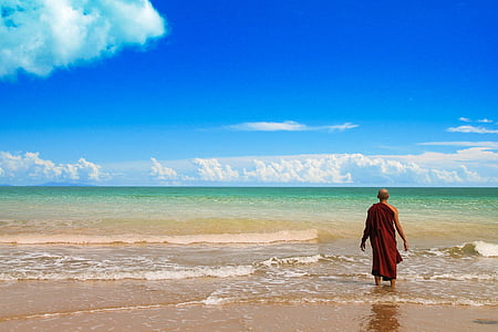 man in red robe standing on beach shore during day time