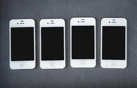 four white 4 iPhone 4's on gray textile