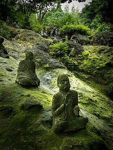 three Buddha figurines on rock