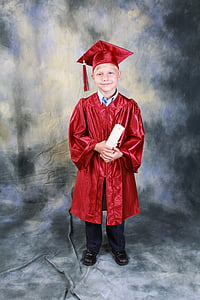 boy in red academic gown holding diploma while standing