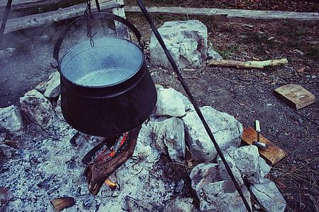 black cooking pot above firewoods