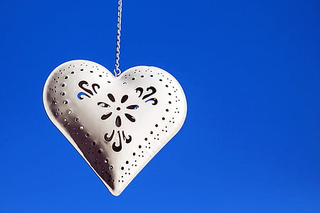 silver-colored heart pendant with chain necklace and blue background