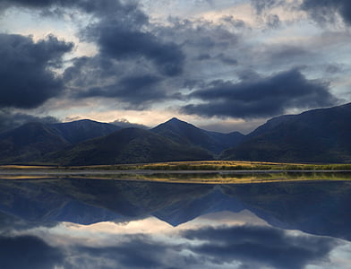 mountain range reflecting on the ocean under cloudy sky