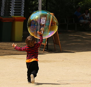 boy playing with bubble during daytime