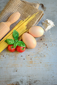 two beige egg near two red tomatoes and beige wooden rolling pin both on gray and beige wooden surface