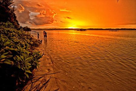 children standing on gray sand next to beach during sunset