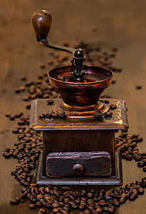 shallow focus photography of brass-colored coffee grinder