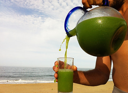 person pouring pitcher in glass beside body of water