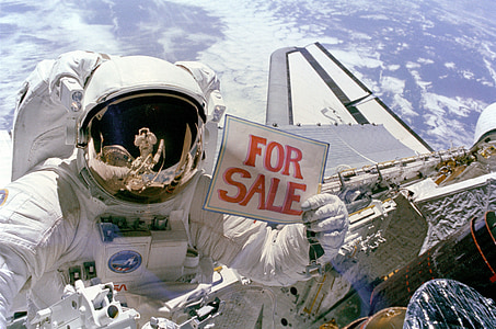 person wearing astronaut suit holding For Sale signage photography