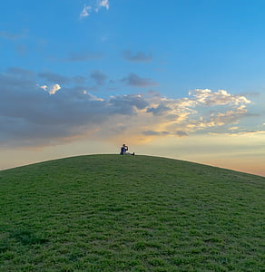 person sitting on top of hills