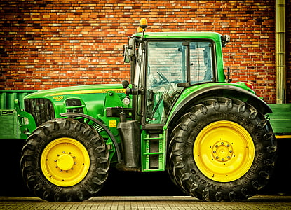 green tractor near brick wall