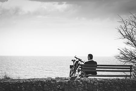 man in black suit jacket beside sea shore
