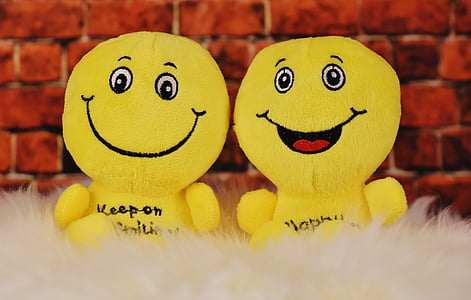 two yellow emoji plush toys
