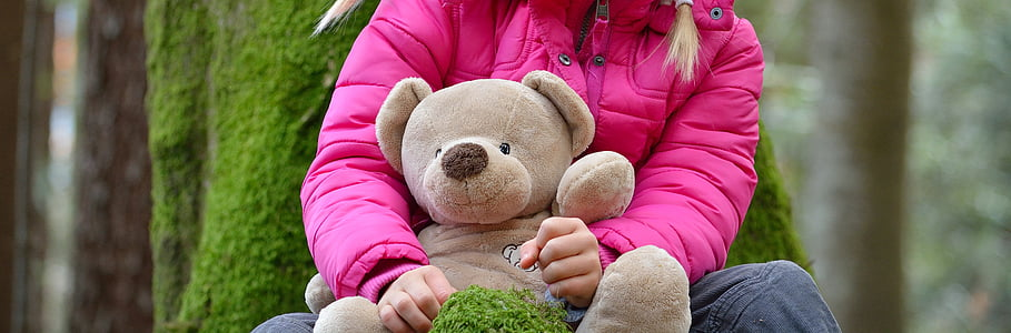 shallow focus photography of person holding bear plush toy