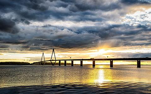 photo of bridge under dark clouds