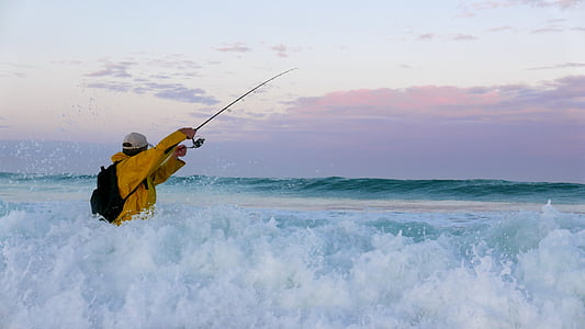 man wearing orange windbreaker jacket holding telescopic fishing rod on sea water