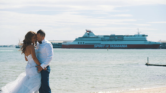 man and woman in wedding clothes overlooking boat on sea