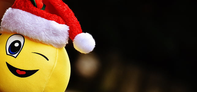selective focus photo of yellow emoticon with Santa hat