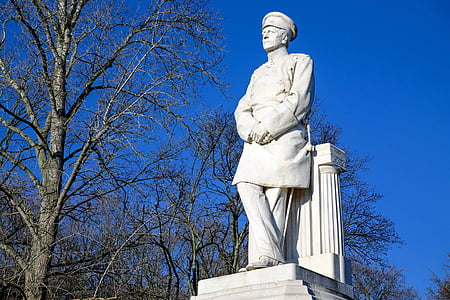 man standing statue beside tree