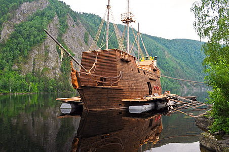 brown wooden ship on body of water at daytime