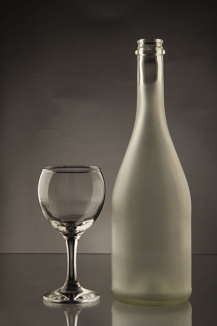 clear glass bottle besides wine glass