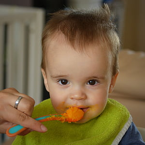 person's left hand holding food filled feeding spoon at baby's mouth