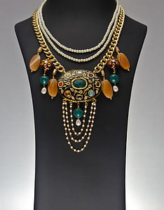 woman's gold-colored fashion necklace on female torso mannequin