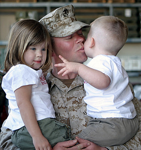 soldier carrying a two babies