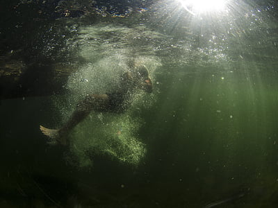 man diving in body of water