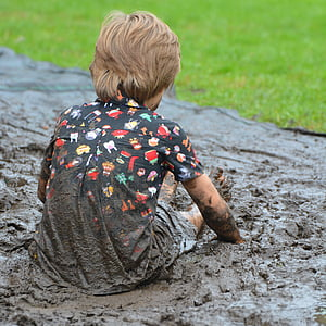 person wearing multicolored shirt while sitting on brown mud