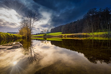 landscape photography of body of water under nimbus clouds
