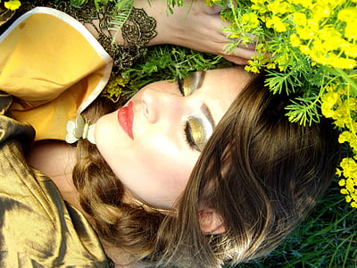 close-up photography of woman in gold-colored eyeliner lying on green grass field