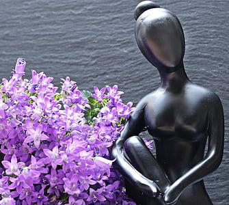 gray metal woman figurine beside purple flowers
