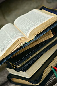 pile of black and blue bibles on brown and white wooden board photo