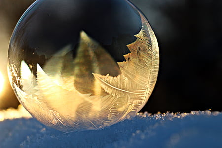 round clear glass ball on top of snow