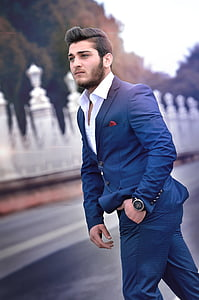 man wearing blue suit jacket and dress pants standing near road