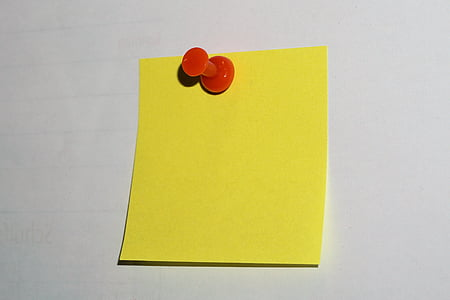 yellow sticky note and red push pin
