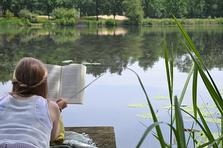 woman reading book on brown dock near lake