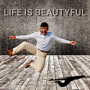 man in white dress shirt and brown dress pants jumping with Life is beautiful text overlay