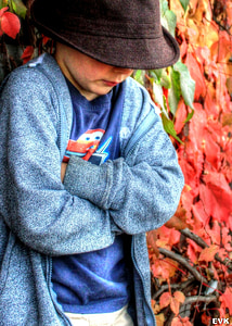shallow focus photography of boy in black hat and blue cardigan