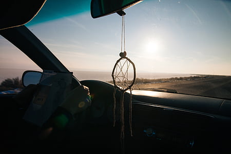 round white rope dream catcher hanged on vehicle rear-view mirror inside vehicle