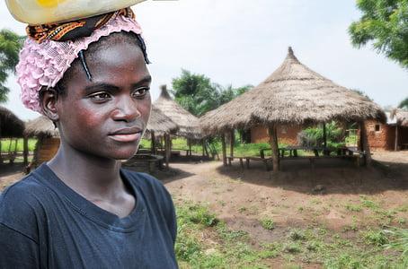 women's black crew-neck shirt near a brown hut at daytime