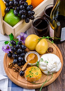 bunch of fruits on brown tray beside labeled glass bottle