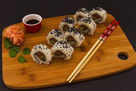white sushi roll on brown wooden chopping board